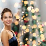 32780429 - smiling woman in evening dress over christmas tree lights background